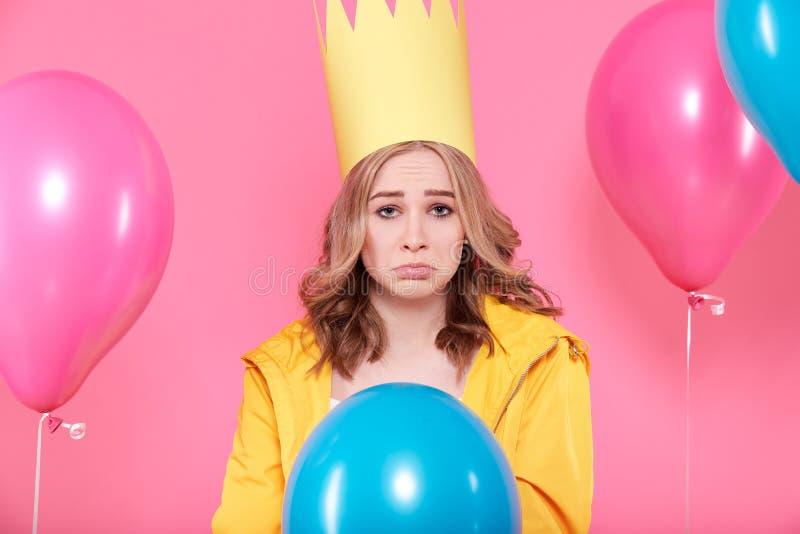 Rozczarowana młoda kobieta w partyjnym kapeluszu otaczającym kolorowymi balonami, odosobniony nadmierny pastelowych menchii tło obraz royalty free
