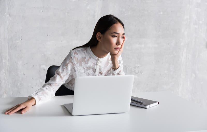 Rozczarowana spogląda kobieta siedzi blisko biurka zdjęcia royalty free