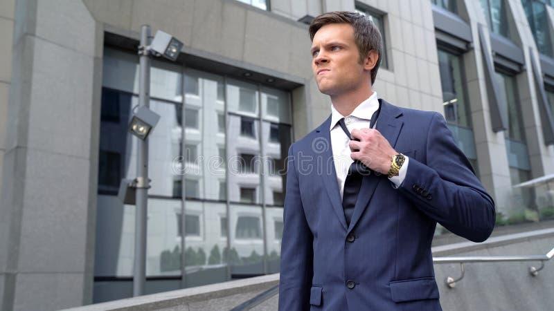 Rozczarowany młodego człowieka ciągnięcia puszka krawat, niepomyślny rozpoczęcie, bezrobocie obrazy stock