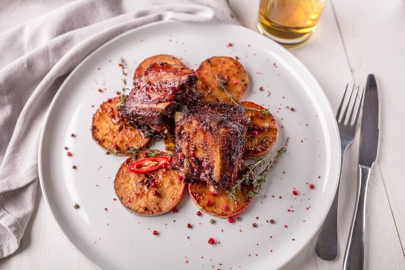 rozdaje gorącego mięso Wieprzowina ziobro piec na grillu z pieprzami i jabłkami zdjęcie stock