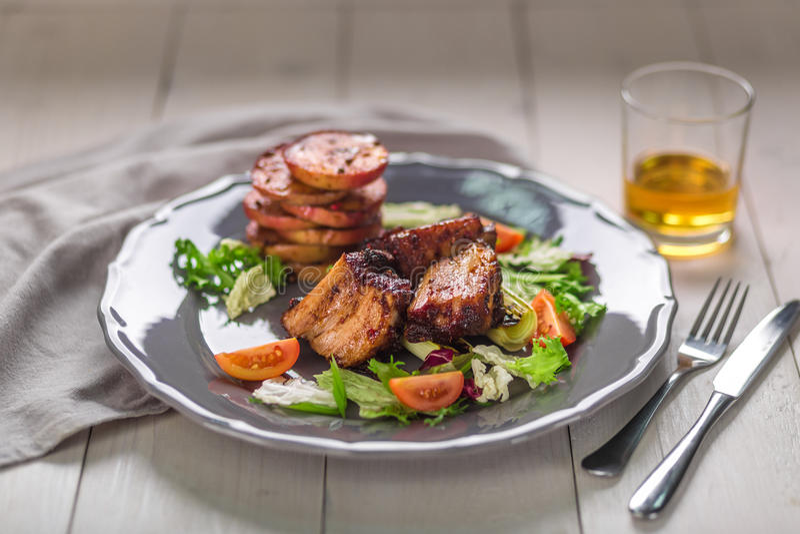 rozdaje gorącego mięso Wieprzowina ziobro piec na grillu z sałatką i jabłkami na talerzu zdjęcia royalty free