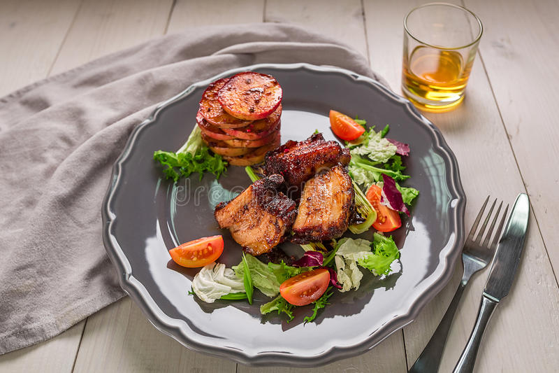 rozdaje gorącego mięso Wieprzowina ziobro piec na grillu z sałatką i jabłkami na talerzu zdjęcie royalty free