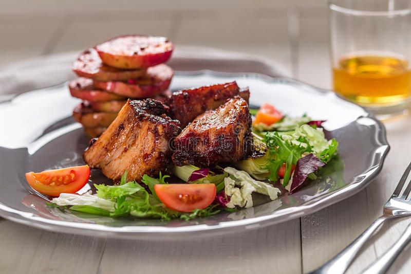 rozdaje gorącego mięso Wieprzowina ziobro piec na grillu z sałatką i jabłkami na talerzu obrazy stock