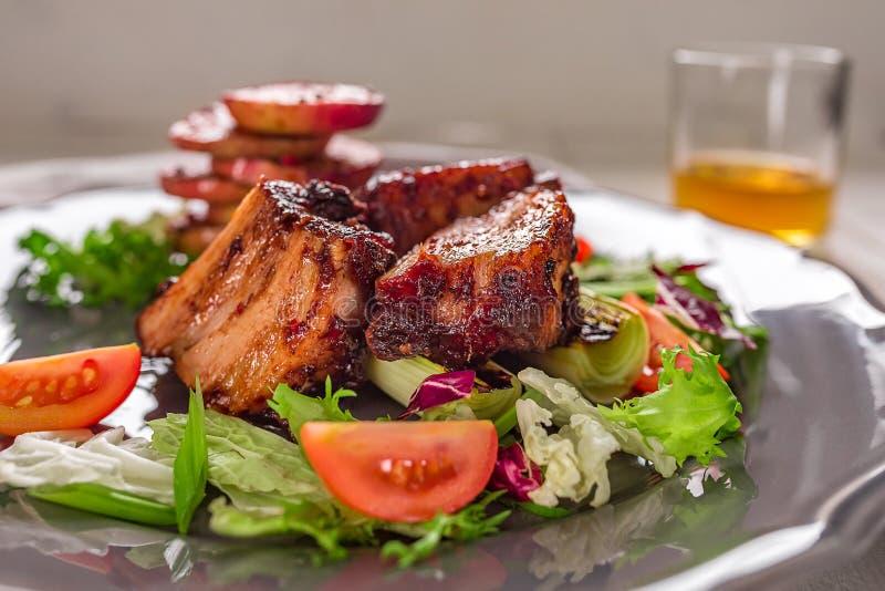 rozdaje gorącego mięso Wieprzowina ziobro piec na grillu z sałatką i jabłkami na talerzu obraz stock