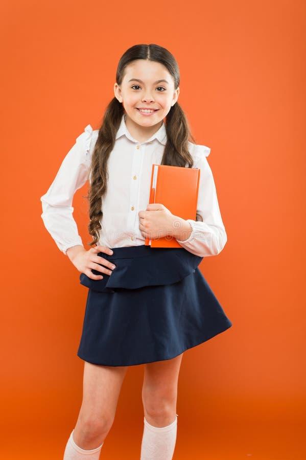 Rozdawa? z szkolnym stresem Znakomity pierwszy poprzedni Dziewczyny dziecka chwyta ksi??ka Szkolny dziewczyny studiowania podr?cz fotografia royalty free