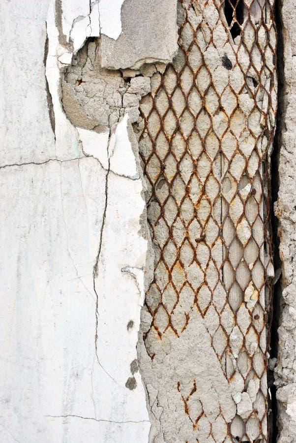 Rozdrabnianie malował w białej betonowej ścianie z ośniedziałą siatką inside fotografia royalty free
