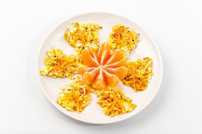 Rozdrapani jajka i pomarańcze kształtowali jak kwiatu odgórny widok obraz royalty free