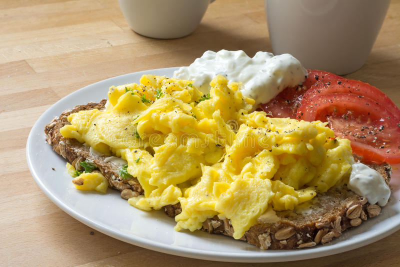 Rozdrapani jajka na nieociosanym chlebie z pomidorami i szorstkim serowym cre obrazy royalty free