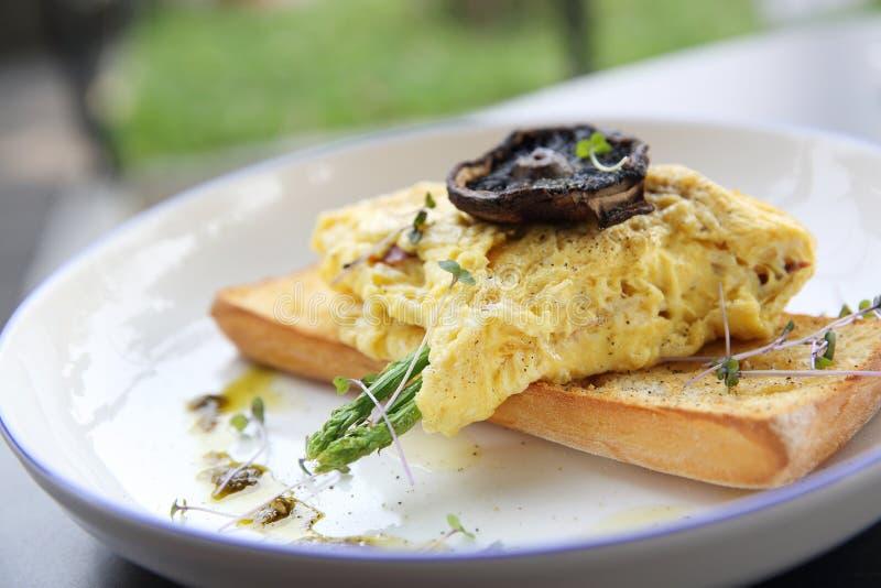 Rozdrapani jajka z chlebowymi asparagusami i pieczarką obraz stock