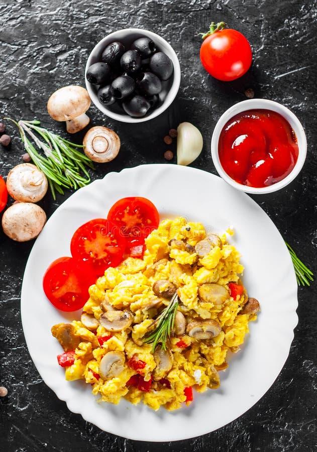 Rozdrapani jajka z pieczarkami i warzywami w bielu talerzu obrazy stock