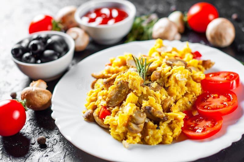 Rozdrapani jajka z pieczarkami i warzywami w bielu talerzu fotografia stock