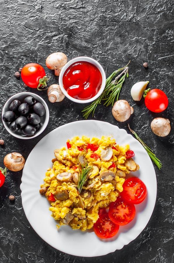 Rozdrapani jajka z pieczarkami i warzywami w bielu talerzu obraz stock