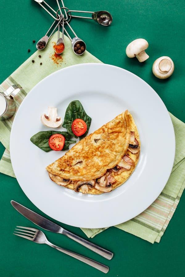 Rozdrapani jajka z pieczarkami słuzyć na bielu talerzu z czereśniowymi pomidorami i szpinakami fotografia stock