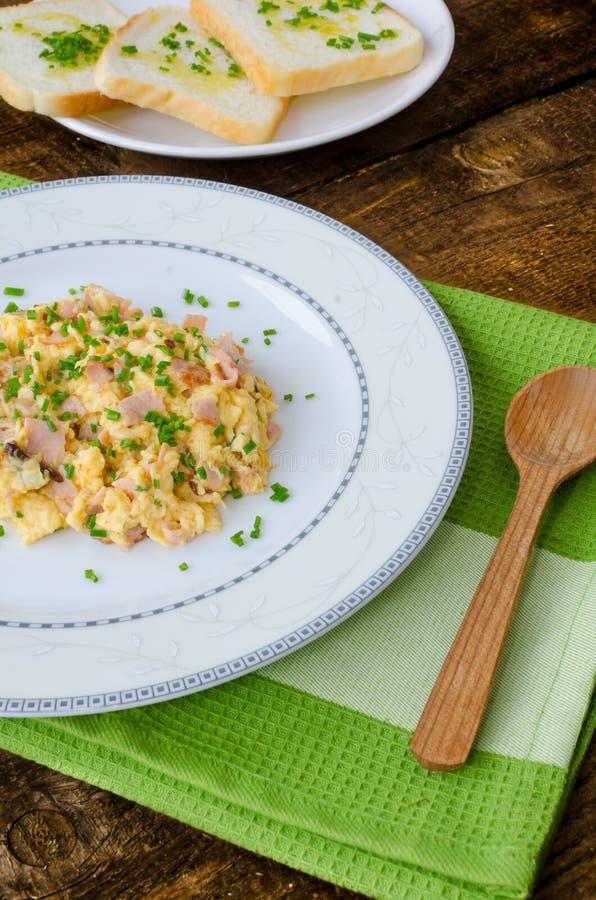 Rozdrapani jajka z szczypiorkiem i bekonem, grzanka z ziele fotografia stock
