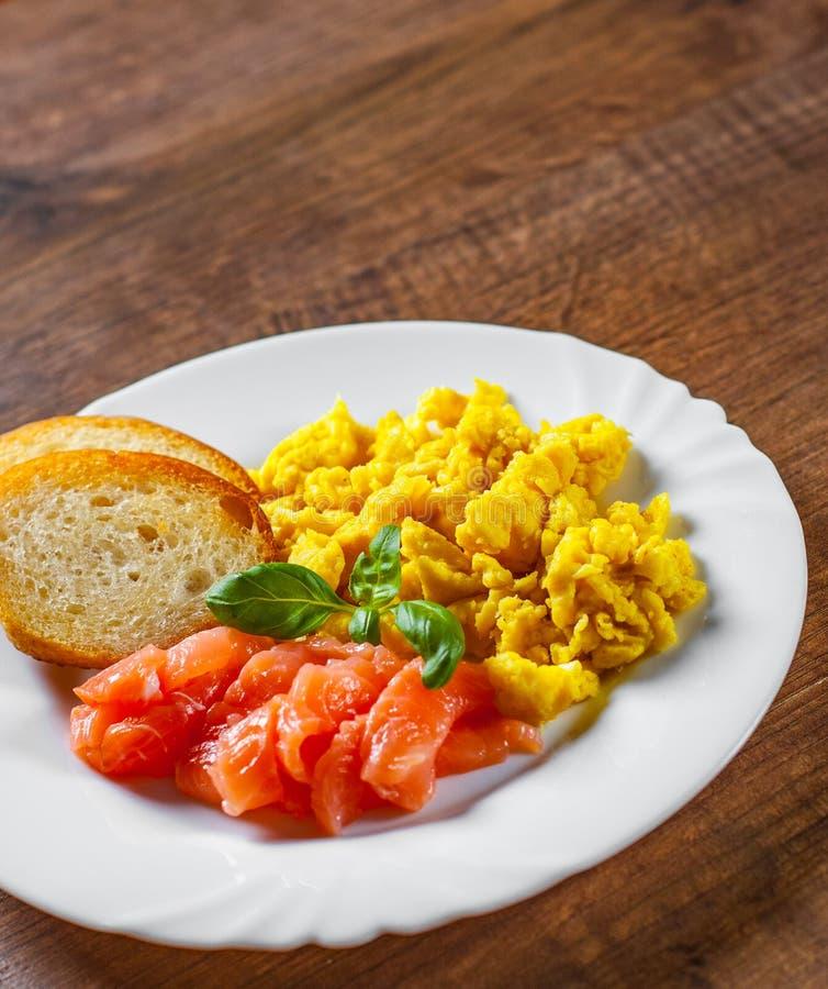 Rozdrapani jajka z uwędzonym łososiem i grzanką w bielu talerzu na drewnianym stole obrazy royalty free