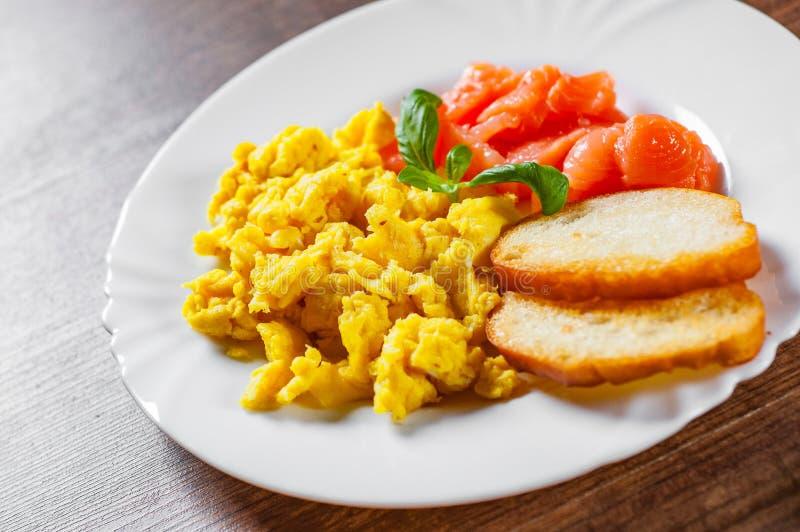 Rozdrapani jajka z uwędzonym łososiem i grzanką w bielu talerzu na drewnianym stole fotografia stock