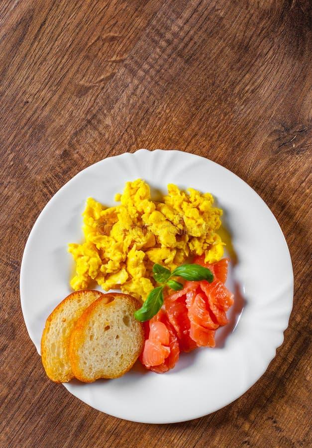 Rozdrapani jajka z uwędzonym łososiem i grzanką w bielu talerzu na drewnianym stole zdjęcia stock