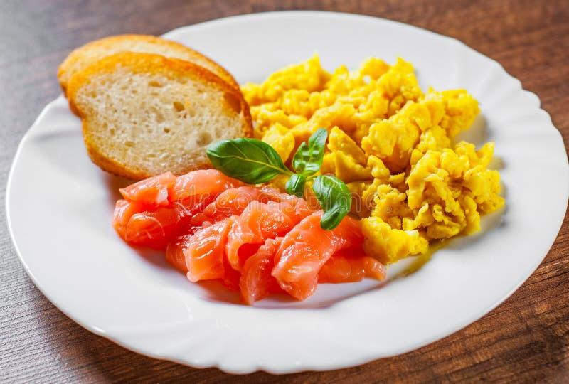Rozdrapani jajka z uwędzonym łososiem i grzanką w bielu talerzu na drewnianym stole fotografia royalty free