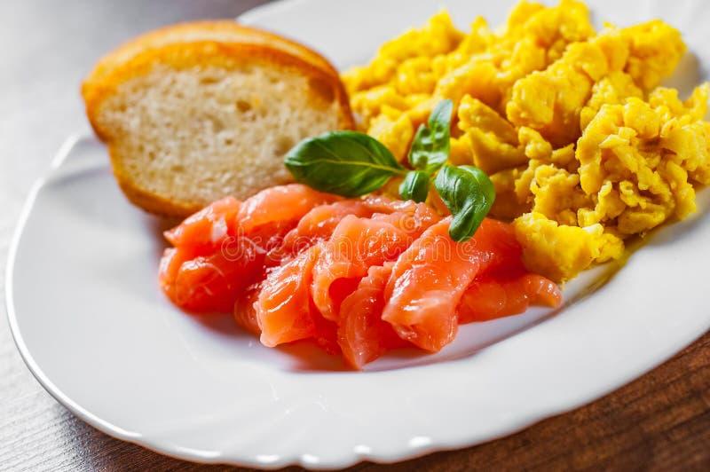 Rozdrapani jajka z uwędzonym łososiem i grzanką w bielu talerzu na drewnianym stole obraz stock
