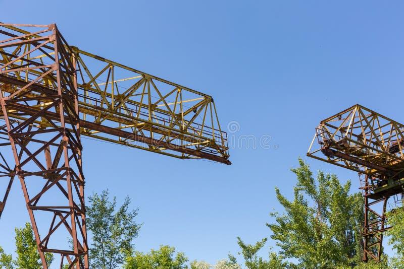 Rozdziela dwa ośniedziałego kętnara żurawia na tle niebieskie niebo zdjęcia stock