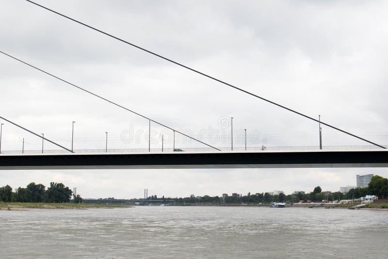 Rozdziela widok i swój budowę przy mostem pod chmurnym niebem przy Rhine riverbank w dà ¼ sseldorf Germany obrazy royalty free