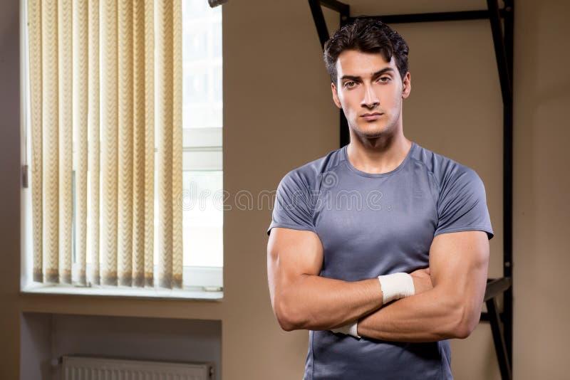 Rozdzierający mięśniowy mężczyzna w gym robi sportom obrazy royalty free