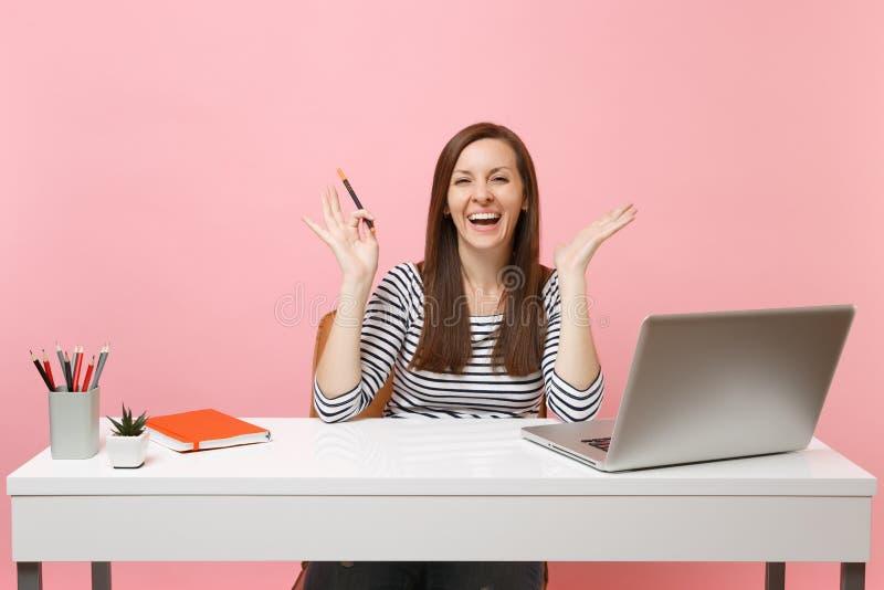 Roześmiana kobieta trzyma ołówkowe podesłanie ręki w przypadkowych ubraniach siedzi, pracuje przy białym biurkiem z współczesnym  zdjęcie stock