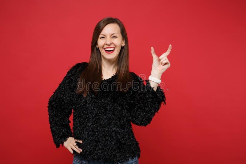 Roześmiana młoda kobieta gestykuluje w czarnym futerkowym pulowerze demonstrujący rozmiar z workspace odizolowywającym na jaskraw obrazy royalty free