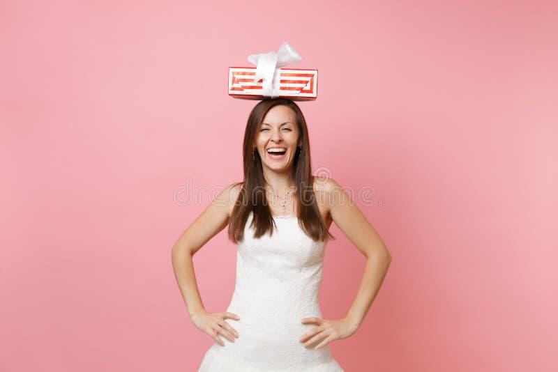 Roześmiana radosna panny młodej kobieta w białej ślubnej sukni pozycji z rękami akimbo, mienie czerwieni pudełko z prezentem, ter fotografia royalty free