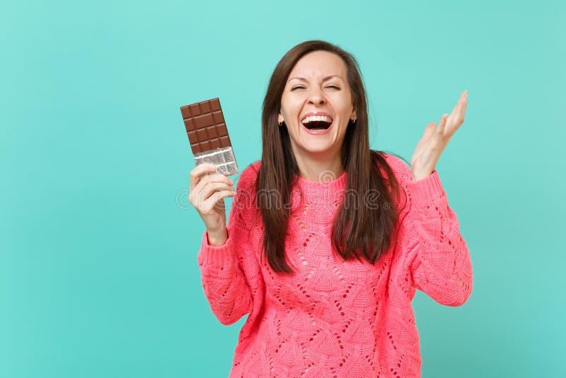 Roześmiana rozochocona młoda kobieta trzyma czekoladowego baru w trykotowym różowym pulowerze, rozprzestrzenia ręki odizolowywać  zdjęcie royalty free