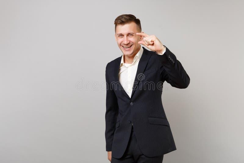 Roześmiany młody biznesowy mężczyzna w klasycznym czarnym kostiumu, koszula gestykuluje demonstrujący rozmiar z kopii przestrzeni fotografia stock