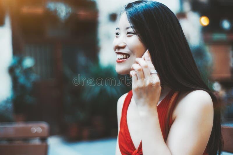 Roześmiana Azjatycka dziewczyna dzwoni outdoors zdjęcie royalty free