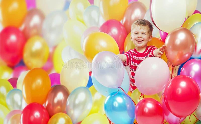 Roześmiana chłopiec bawić się wśród baloons obrazy stock