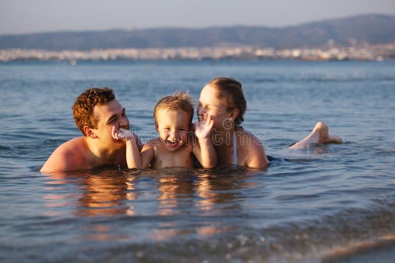 Roześmiana chłopiec z jego wychowywa przy morzem zdjęcie royalty free