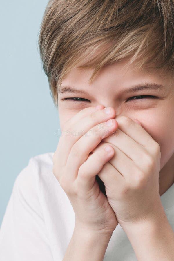 Roześmiana chłopiec zakrywa jego usta z jego rękami fotografia royalty free