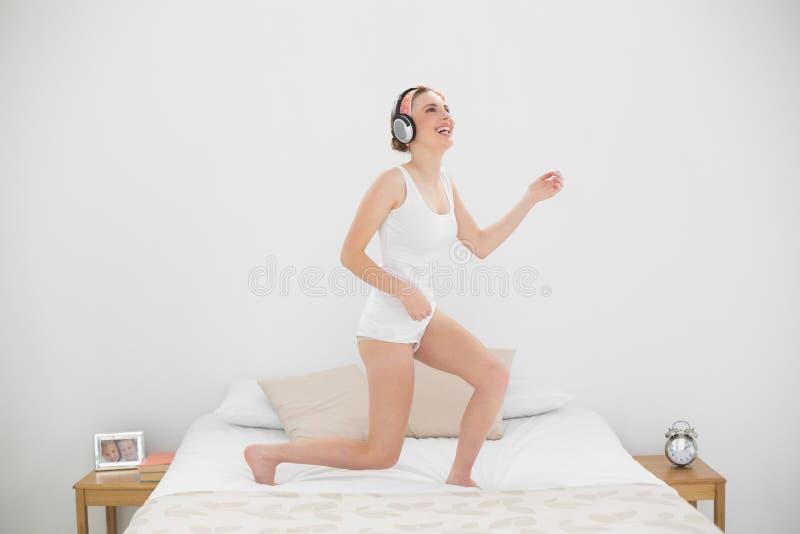 Roześmiana kobieta bawić się lotniczą gitarę podczas gdy słuchający muzyka obrazy royalty free