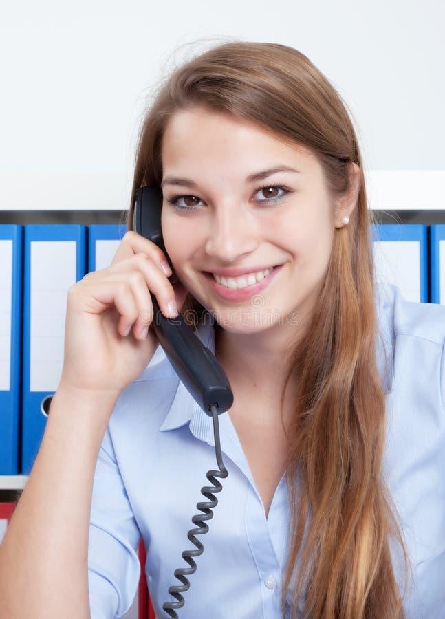 Roześmiana kobieta opowiada przy telefonem z długim blondynem przy biurem obraz stock