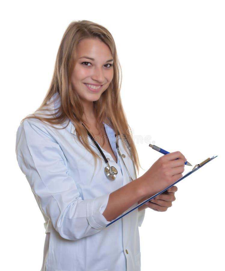 Roześmiana kobiety lekarka z blondynem i schowkiem fotografia stock