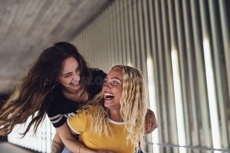 Roześmiana młoda kobieta niesie jej dziewczyny na ona z powrotem obrazy royalty free