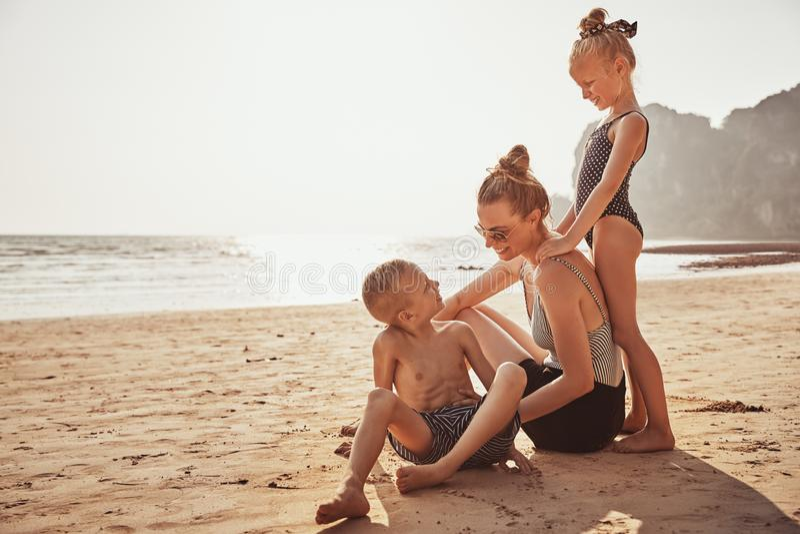 Roześmiana matka i dzieci siedzi na piaskowatej plaży zdjęcia royalty free