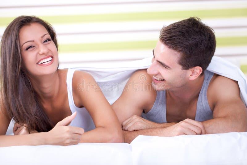 Roześmiana para w łóżku zdjęcia royalty free