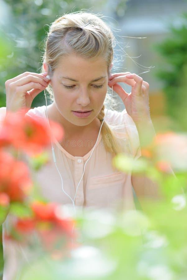 Roześmiana piękna młoda kobieta z hełmofonami w parku zdjęcia royalty free
