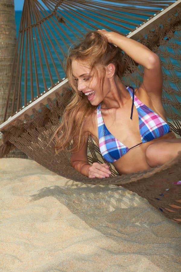 Roześmiana szczęśliwa kobieta opiera w hamaku zdjęcie royalty free