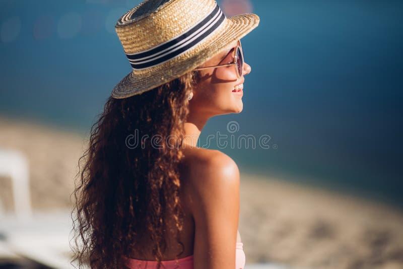 Roześmiana wolności kobieta, Chłodno modniś dziewczyna w lato słomianym kapeluszu pozuje obok egzotycznej lato plaży lata mody go zdjęcia royalty free