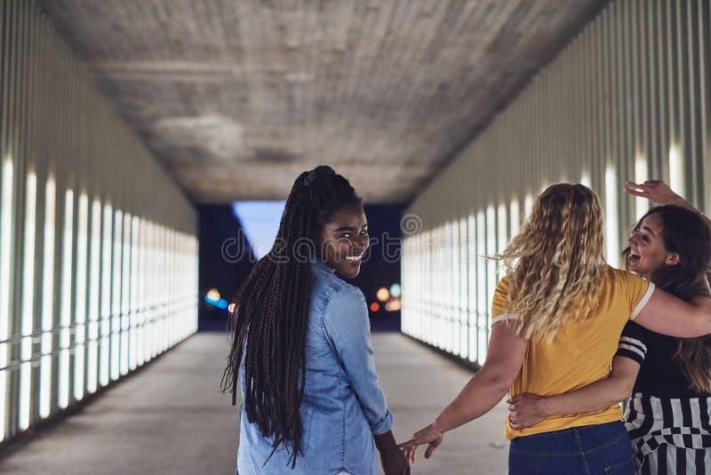 Roześmiane młode kobiety chodzi w mieście przy nocą obraz stock