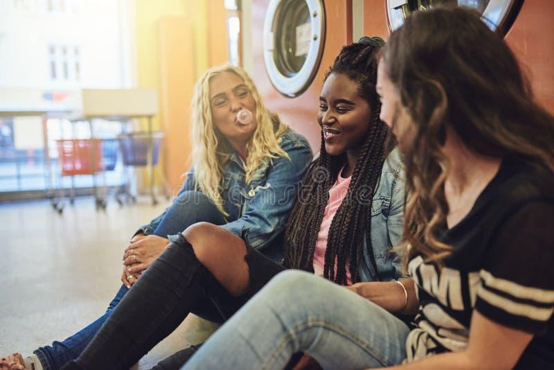 Roześmiane młode kobiety wiszące za wpólnie na laundromat podłodze zdjęcie royalty free