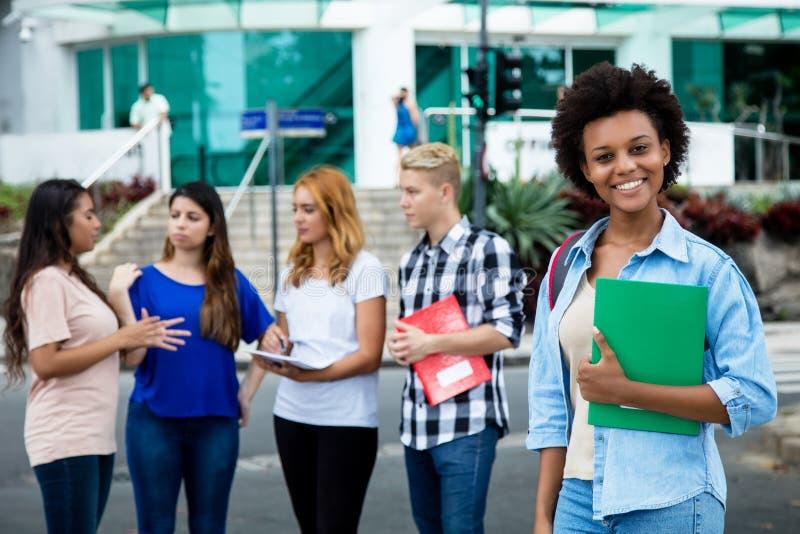 Roześmianego amerykanina afrykańskiego pochodzenia żeński uczeń z grupą internati obraz royalty free