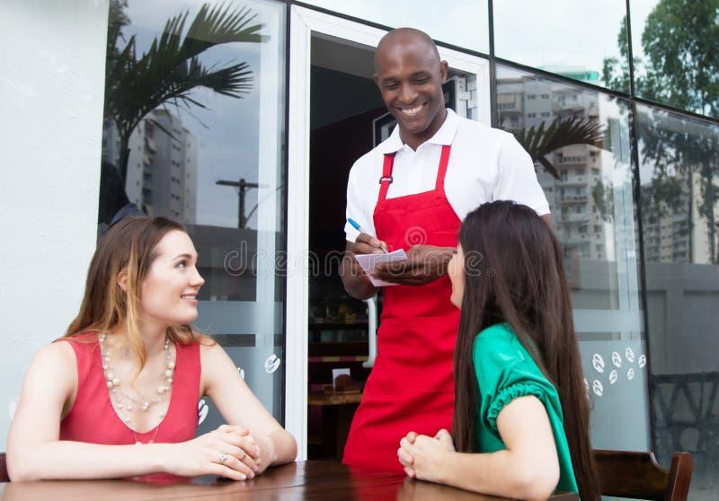 Roześmianego amerykanina afrykańskiego pochodzenia kelnera powitalni goście obrazy stock