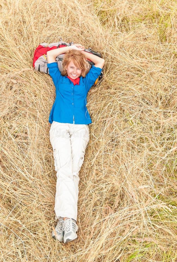 Roześmianej kobiety łgarski puszek na trawie w łące. obrazy stock