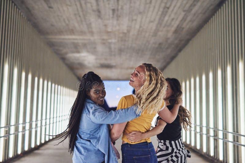 Roześmiani młodzi żeńscy przyjaciele chodzi wpólnie w mieście obraz stock